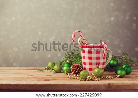 Christmas holiday decorations with checked cup and candy on wooden table - stock photo