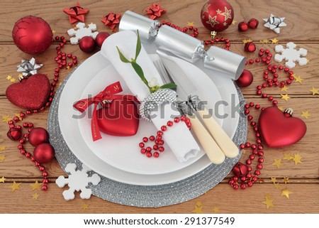 Christmas holiday dinner place setting with plates, antique cutlery, napkin, bauble decorations and mistletoe over oak background. - stock photo