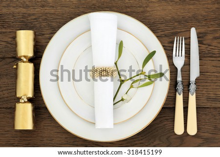 Christmas holiday dinner place setting with plates, napkin, cutlery and mistletoe over old oak table background.