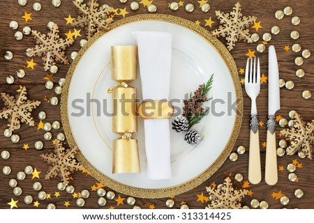 Christmas holiday dinner place setting with plates, napkin, cutlery, gold bauble decorations over oak table background. - stock photo