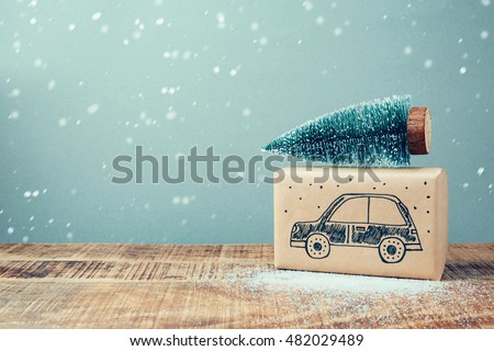 Christmas holiday gift box with car drawing and pine tree on wooden table