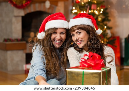 Christmas holiday happy girl friends exchanging presents in christmas decorated living room ,wear red new year santa hat, over chimney and christmas tree colorful lights background - stock photo