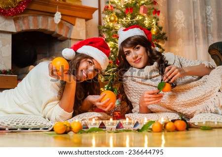 Christmas holiday happy girl friends playing with orange fruits , wearing red new year santa hat, over chimney and christmas tree colorful lights background.