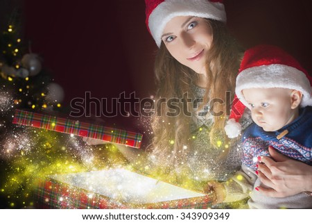 Christmas holiday! Mom opens the magic box with a gift for child. Out of the box shining light. The kid looking at the box with interest. Mom and baby in Santa hats - stock photo