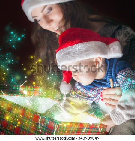 Christmas holiday! Mother with baby opens the magic box with gift. Box full of magic surprises and secrets! The kid looking at the box with interest. Mom and baby in Santa hats. Happy family concept - stock photo