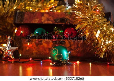 Christmas holiday reddish treasure box with colorful decorative balls inside of it, fir on, and close up on a green ball in front