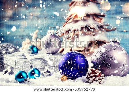 Christmas holiday setting with festive decorations in silver tone laying in snow. Christmas background