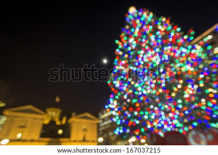 Christmas Holiday Tree with Moon at Pioneer Courthouse Square in Portland Oregon Downtown with Blur Defocused Bokeh Colorful Lights at Night - stock photo