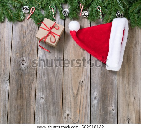 Christmas holiday wooden background with fir branches, Santa cap and gift box forming upper border