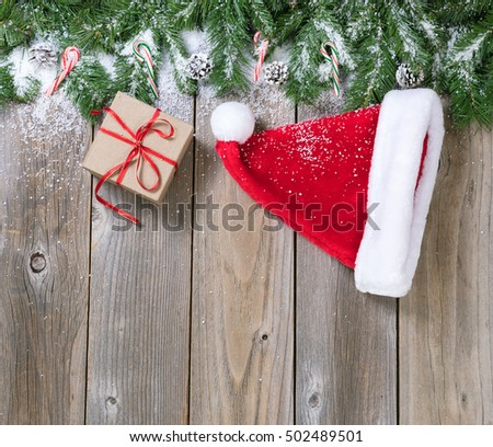 Christmas holiday wooden background with fir branches, snow, Santa cap and gift box forming upper border