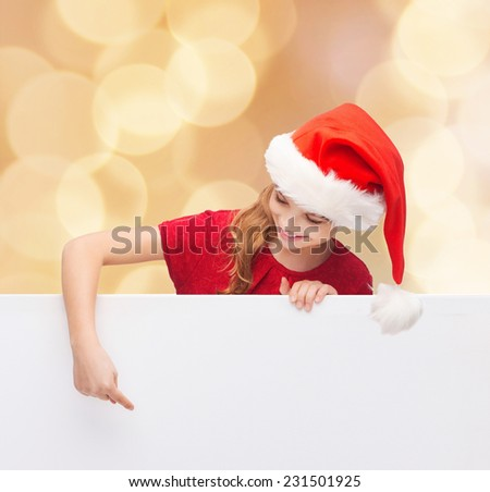 christmas, holidays and advertisement concept - happy girl in santa helper hat pointing finger on blank white board over beige lights background