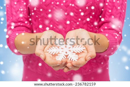 christmas, holidays and people concept - close up of woman in pink sweater holding snowflake decoration over blue background with snow - stock photo