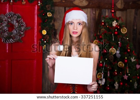 Woman in red dress with white blank over christmas tree background