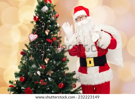christmas, holidays and people concept - man in costume of santa claus with bag and christmas tree waving hand over beige lights background