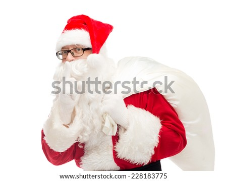 christmas, holidays and people concept - man in costume of santa claus with bag making hush gesture