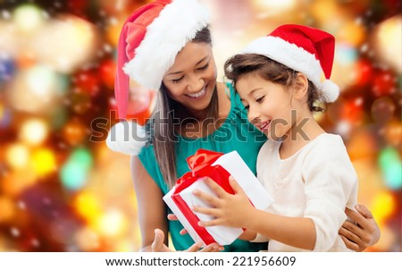 christmas, holidays, celebration, family and people concept - happy mother and little girl in santa helper hats with gift box over red lights background