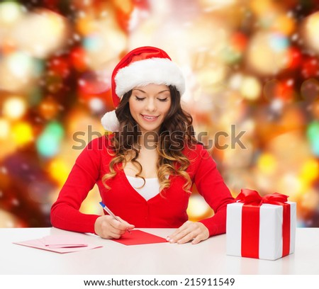 christmas, holidays, celebration, greeting and people concept - smiling woman in santa helper hat with gift box writing letter or sending post card over red lights background - stock photo
