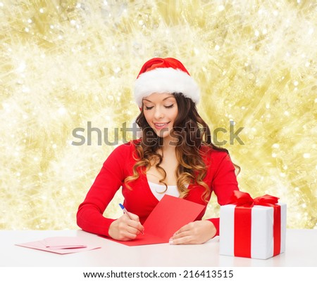 christmas, holidays, celebration, greeting and people concept - smiling woman in santa helper hat with gift box writing letter or sending post card over yellow lights background - stock photo