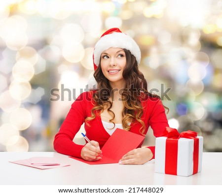 christmas, holidays, celebration, greeting and people concept - smiling woman in santa helper hat with gift box writing letter or sending post card over lights background - stock photo