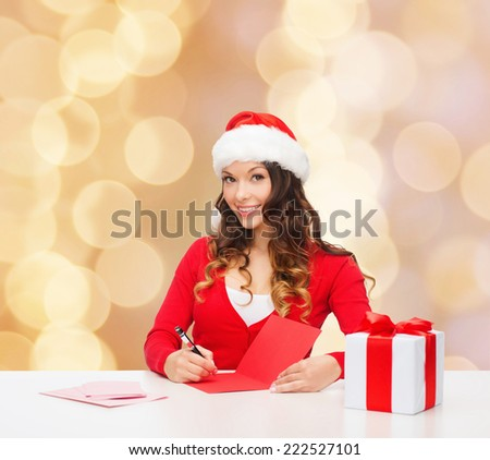 christmas, holidays, celebration, greeting and people concept - smiling woman in santa helper hat with gift box writing letter or sending post card over beige lights background - stock photo