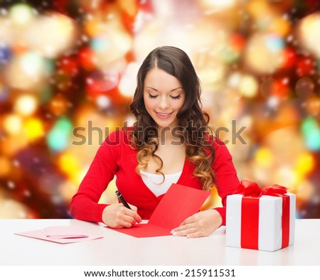 christmas, holidays, celebration, greeting and people concept - smiling woman with gift box writing letter or sending post card over red lights background - stock photo