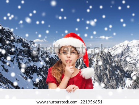 christmas, holidays, childhood and people concept - smiling little girl in santa helper hat with finger on her lips over snowy mountains background