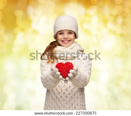 christmas, holidays, childhood, presents and people concept - dreaming girl in winter clothes with red heart over yellow lights background - stock photo