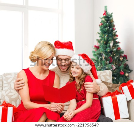 christmas, holidays,  family and people concept - happy mother, father and little girl in santa helper hats with gift boxes reading geeting card over living room and christmas tree background