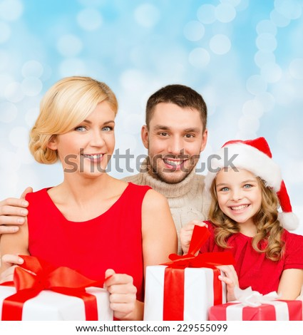 christmas, holidays, family and people concept - happy mother, father and little girl in santa helper hat with gift boxes over blue lights background