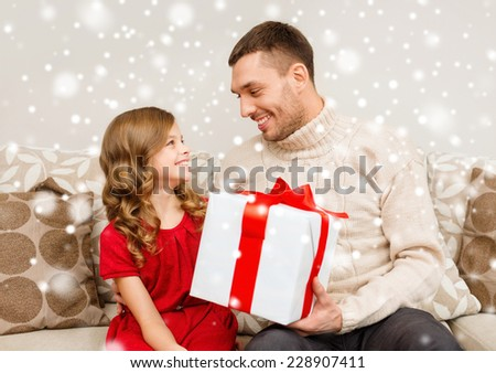 christmas, holidays, family and people concept - smiling father and daughter holding gift box at home