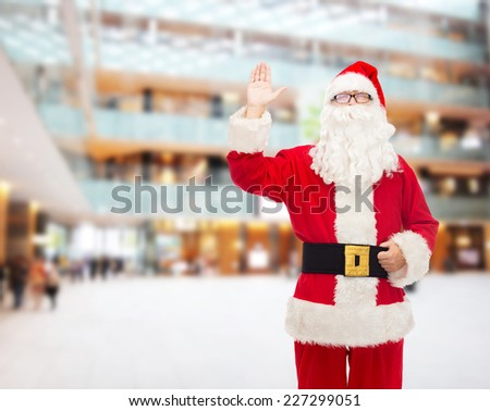 christmas, holidays, gesture and people concept - man in costume of santa claus waving hand over shopping center background - stock photo