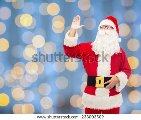 christmas, holidays, gesture and people concept - man in costume of santa claus waving hand over blue lights background - stock photo