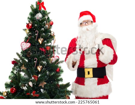 christmas, holidays, gesture and people concept - man in costume of santa claus with bag and christmas tree showing thumbs up - stock photo