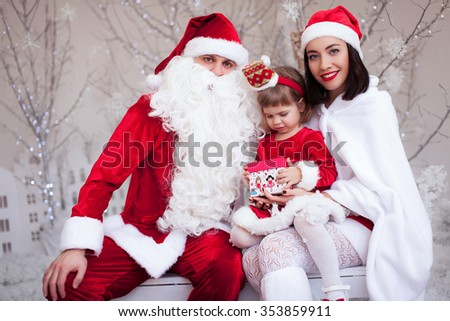 christmas, holidays, happiness and people concept - smiling family in santa helper hats with a gift in the snow wood - stock photo