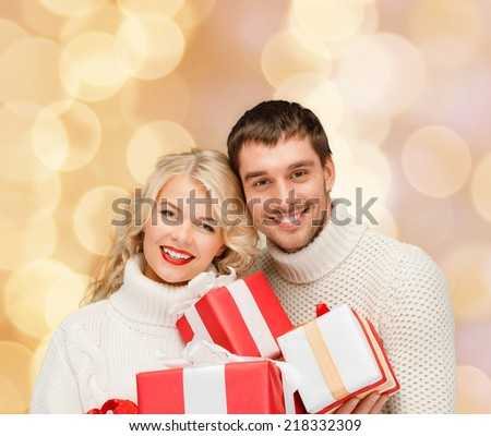christmas, holidays, happiness and people concept - smiling man and woman with presents over beige lights background