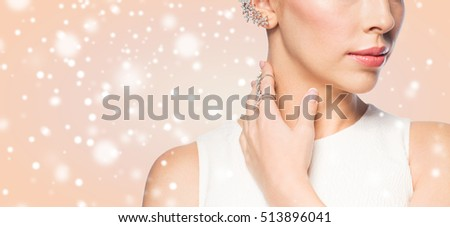 christmas, holidays, jewelry, people and luxury concept - close up of beautiful woman with golden ring and diamond earring over beige background