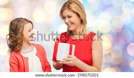 christmas, holidays, people and family concept - smiling mother and daughter with gift box - stock photo
