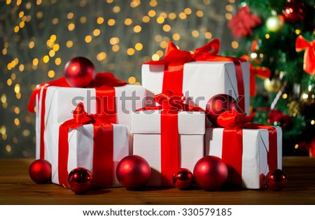 christmas, holidays, presents, new year and celebration concept - group of gift boxes and red balls under x-mas tree on wooden floor - stock photo