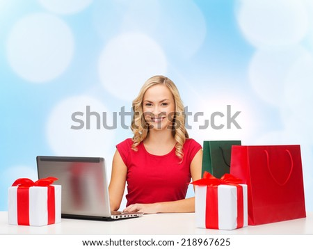 christmas, holidays, technology, advertising and people concept - smiling woman in red blank shirt with shopping bags, gifts and laptop computer over blue lights background