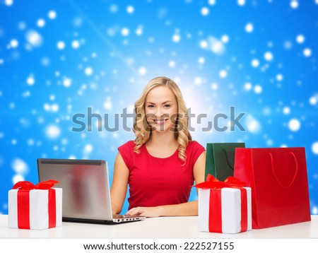 christmas, holidays, technology, advertising and people concept - smiling woman in red blank shirt with shopping bags, gifts and laptop computer over blue snowing background