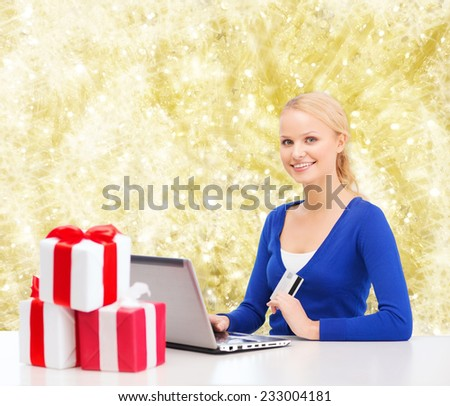 christmas, holidays, technology and shopping concept - smiling woman with gift boxes, credit card and laptop computer over yellow lights background - stock photo