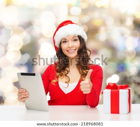 christmas, holidays, technology, gesture and people concept - smiling woman in santa helper hat with gift box and tablet pc computer showing thumbs up over lights background - stock photo