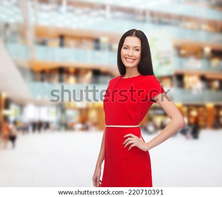 christmas, holidays, valentine's day, celebration and people concept - smiling woman in red dress over shopping center background - stock photo