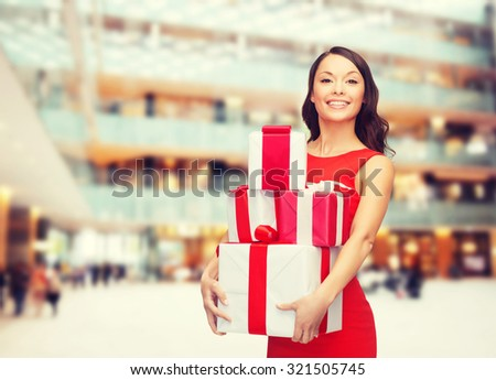christmas, holidays, valentine's day, celebration and people concept - smiling woman in red dress with gift boxes over shopping center background - stock photo