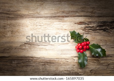 Christmas holly on wooden background - stock photo