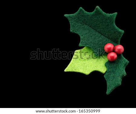 Christmas holly with with red berries isolated on a black background as a winter holiday symbol and seasonal decoration. - stock photo