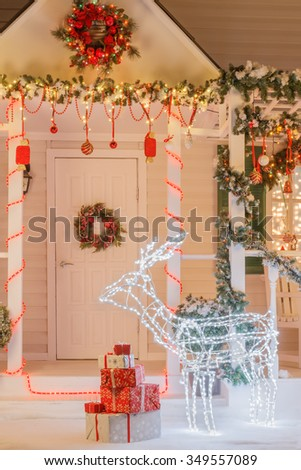 Christmas home exterior decorated with illuminated deer, lights, toys and greenery - stock photo