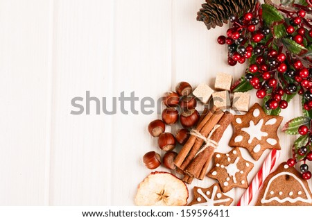 Christmas homemade gingerbread cookies,spice and decoration over white wooden board - stock photo