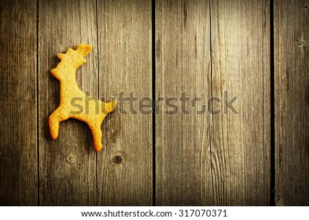 Christmas homemade gingerbread deer over wooden table - stock photo