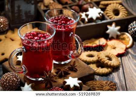 Christmas hot cranberry tea and cookies on dark table, horizontal